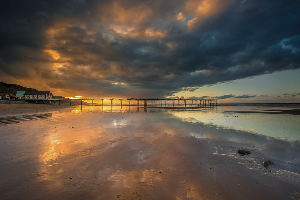 Sunset over Saltburn Pier, the wet sand reflecting the sky.