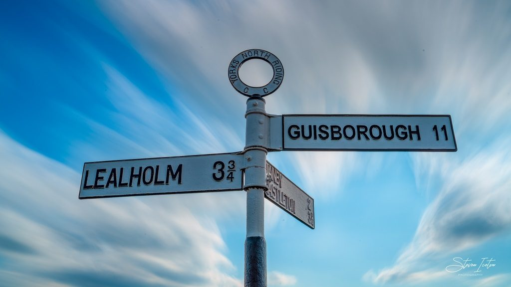 A long exposure photograph of the clouds moving over the old signposts at Danby.